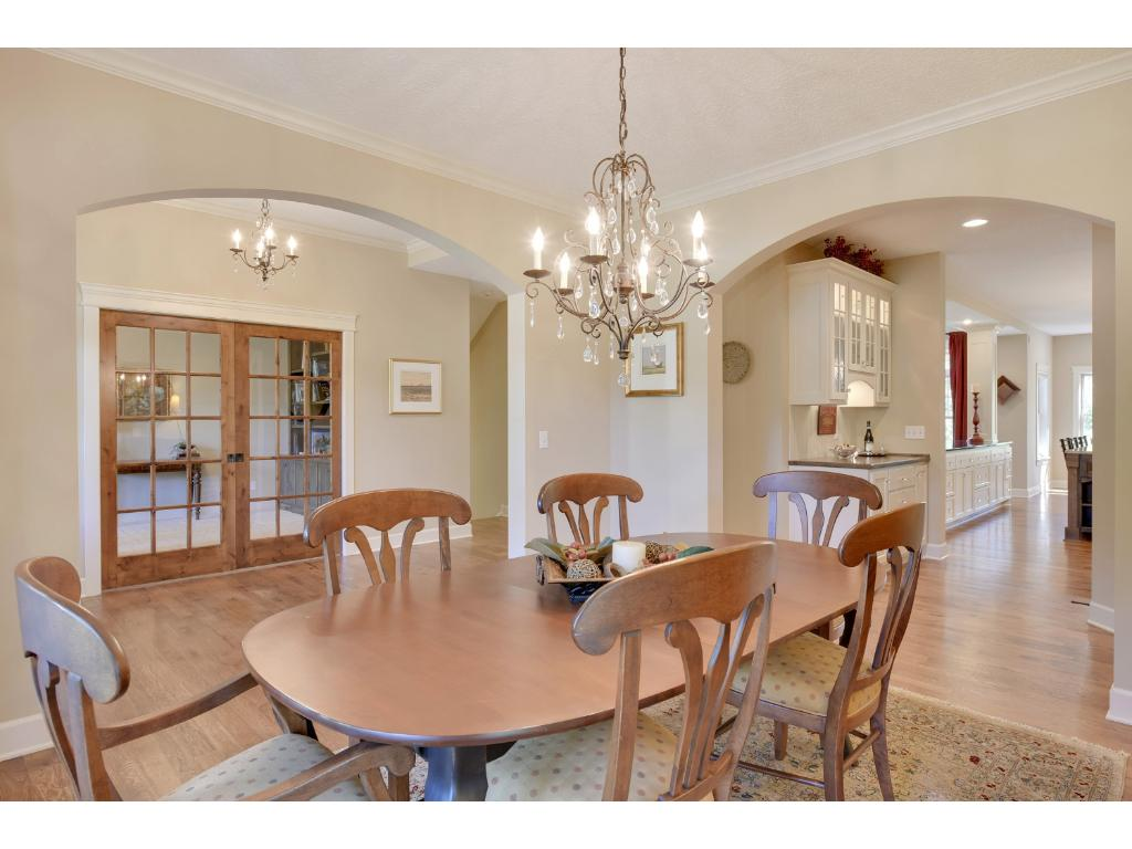 Two large arched walkways enter into the formal dining room featuring crown moulding, hickory hardwood flooring, and beautiful butler's pantry.