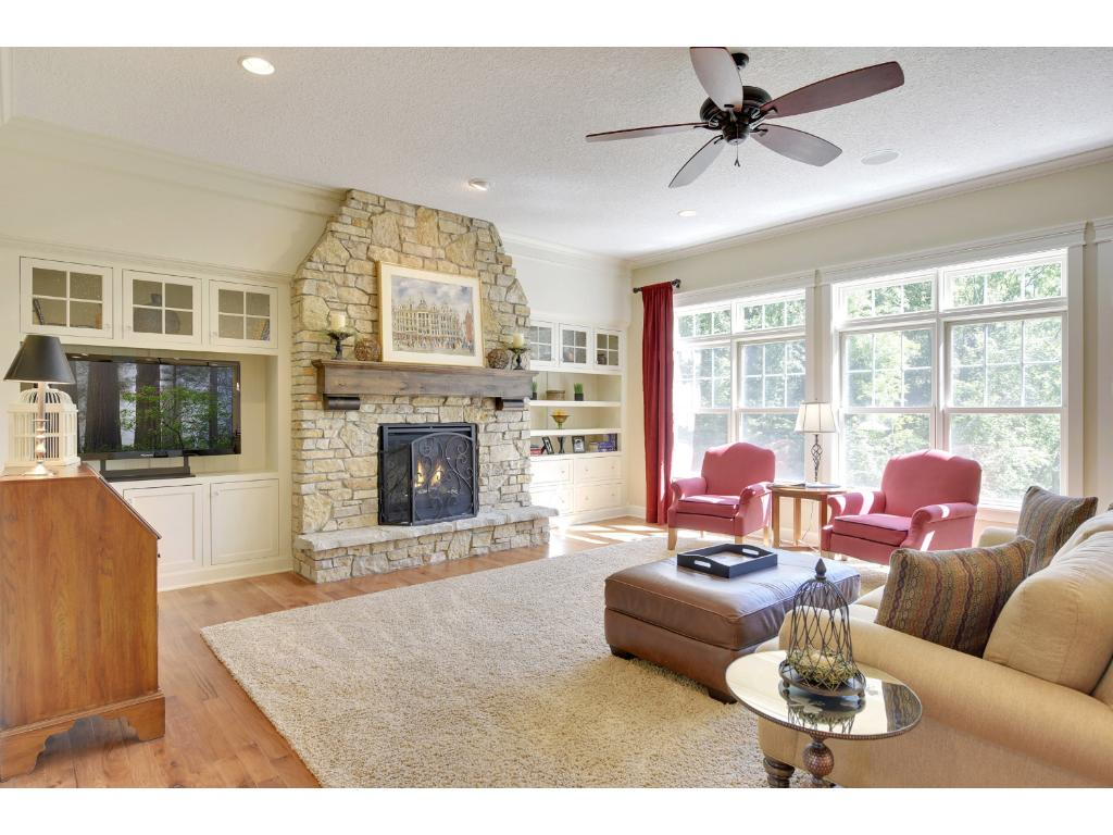 The wide walkway from the foyer opens to the great room offering hickory hardwood flooring, cozy gas fireplace with stone surround and built-in media center and cabinetry.