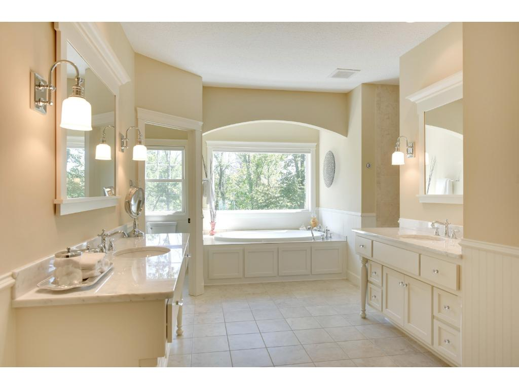 Beautifully finished, the owners' bath showcases dual vanities with Carrera marble counters, arched alcove with jetted tub, walk-in spa-like shower and large walk-in closet with built-in organizers.