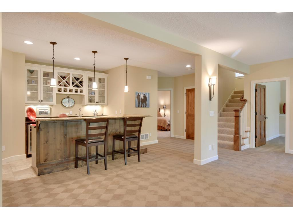 The wet bar is nicely appointed with raised knotty alder bar, granite counters, glass door cabinetry, sink and beverage cooler.