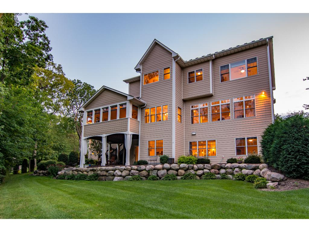 The back of the home features banks of windows allowing the one-of-a-kind wooded, sanctuary views to fill the spaces inside the home.