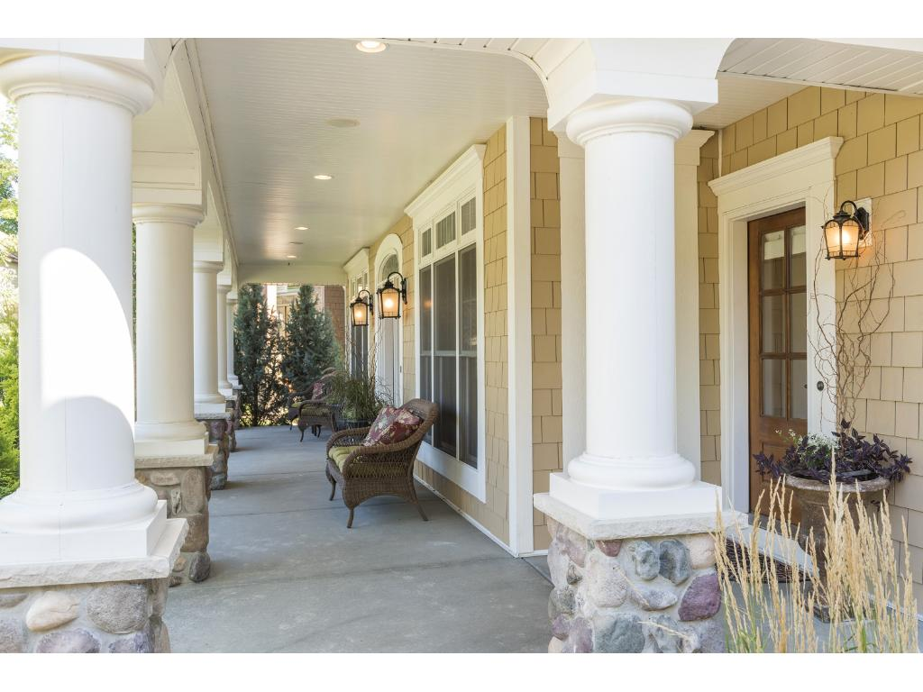 Enchanting front porch with built-in zoned speakers extends the length of the home offering several seating options.