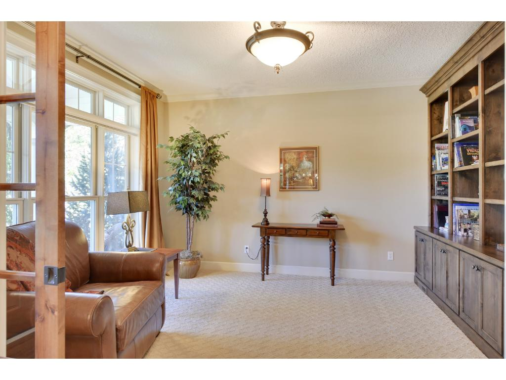 Convenient main floor library features a double French pocket door entrance & a wall of built-in knotty alder cabinetry & bookcases