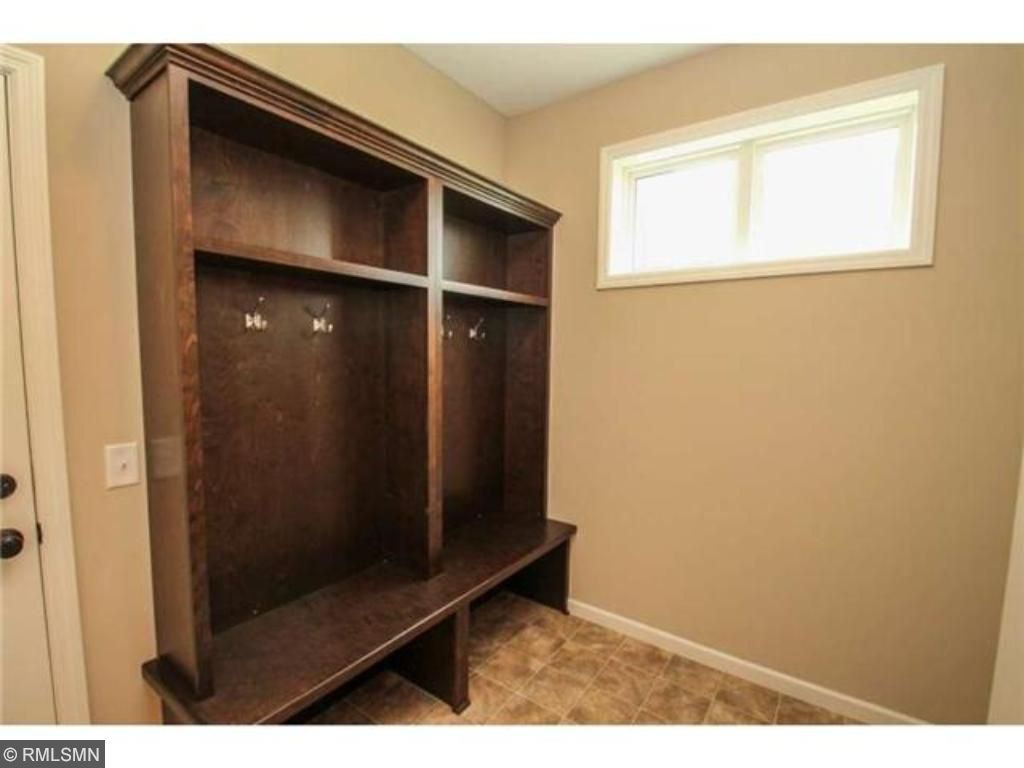 Large mud room with lockers and bench,  1/2 bath and a large walk in closet.