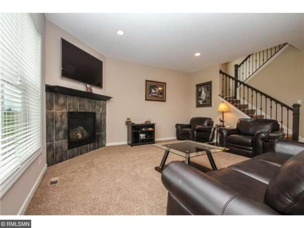 Charming living room with open stairway to the upper level.  Triple window with Hunter Douglas blinds