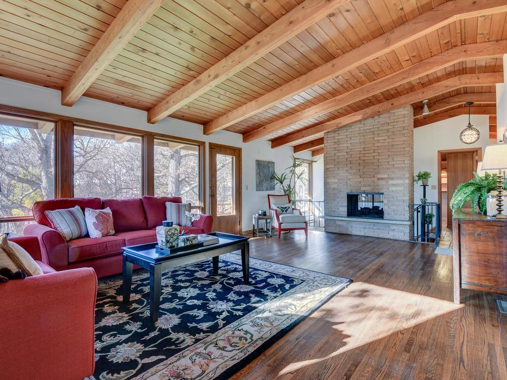 Vaulted wood ceilings, walls of windows and exposed hardwood floors give a warm and casual feel