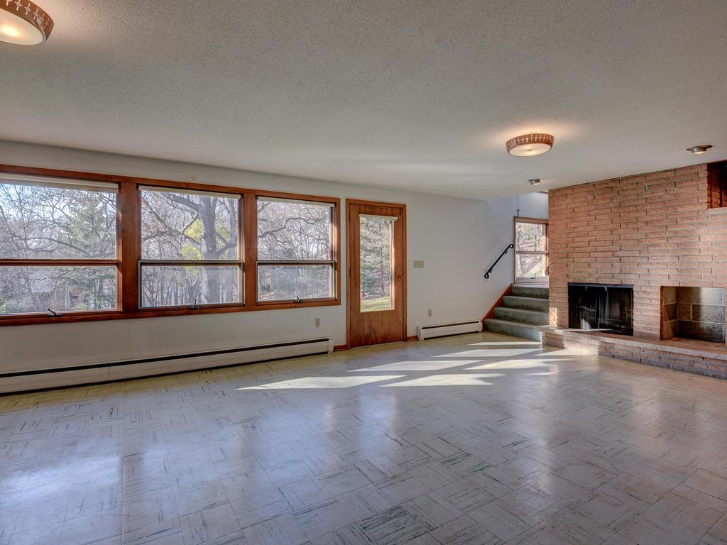 Large family room on the walk-out lower level with another wood-burning fireplace and walls of west facing windows