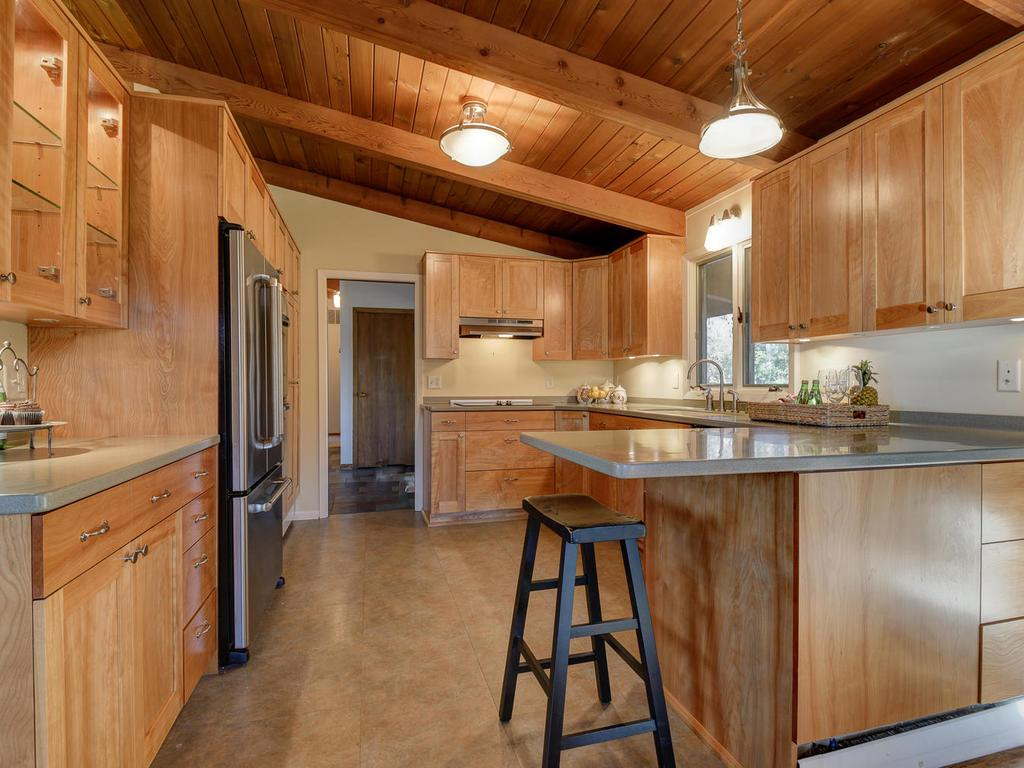 Silestone countertops, stainless appliances, built-in cabinetry with desk and under-cabinet lighting