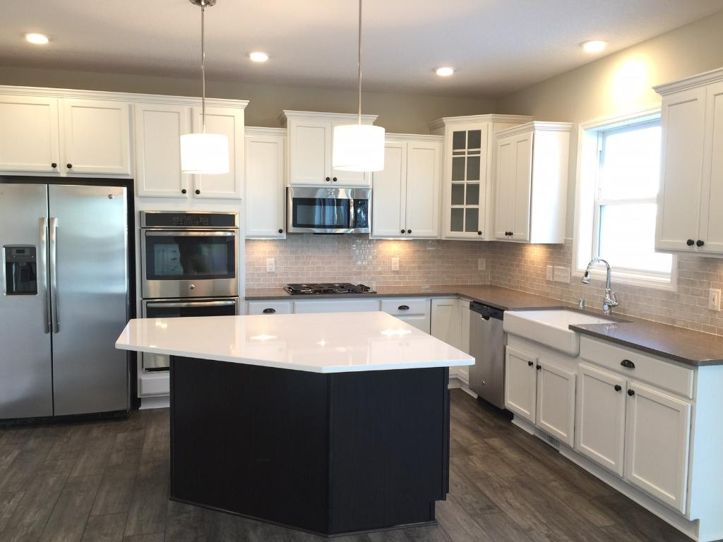 The gourmet kitchen includes a suite of stainless steel GE appliances.  We've also added quartz counter-tops, tile backsplash, Kohler farm sink and undercabinet lighting.