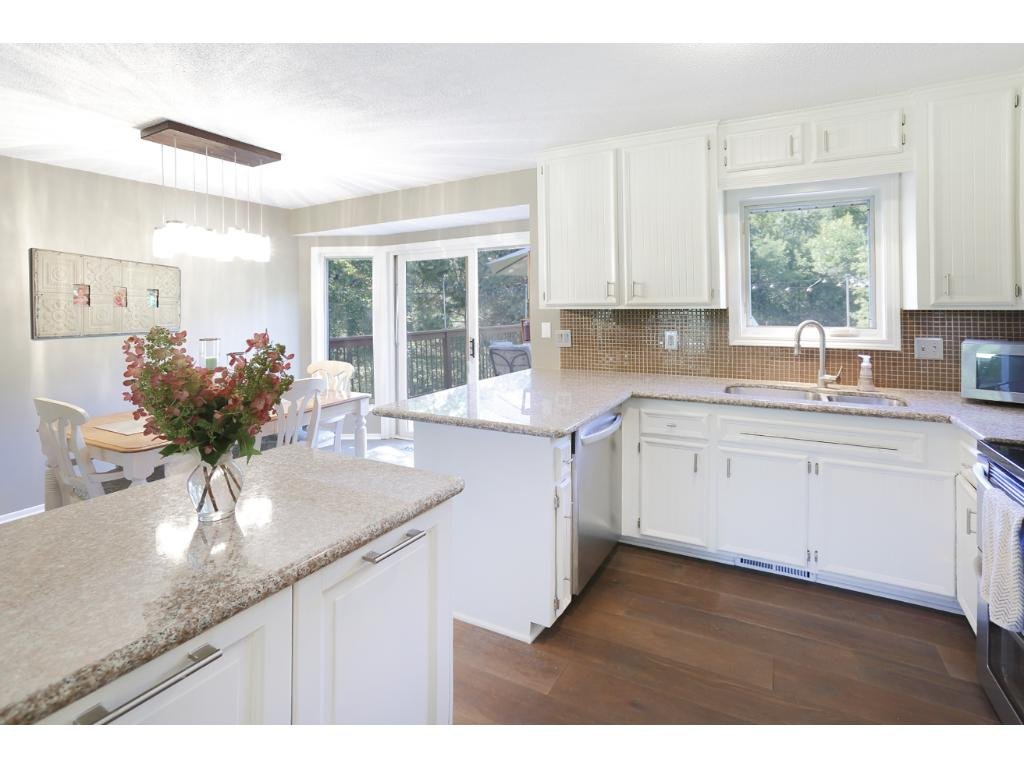 The kitchen is bright and modern with white cabinetry and a unique movable island.