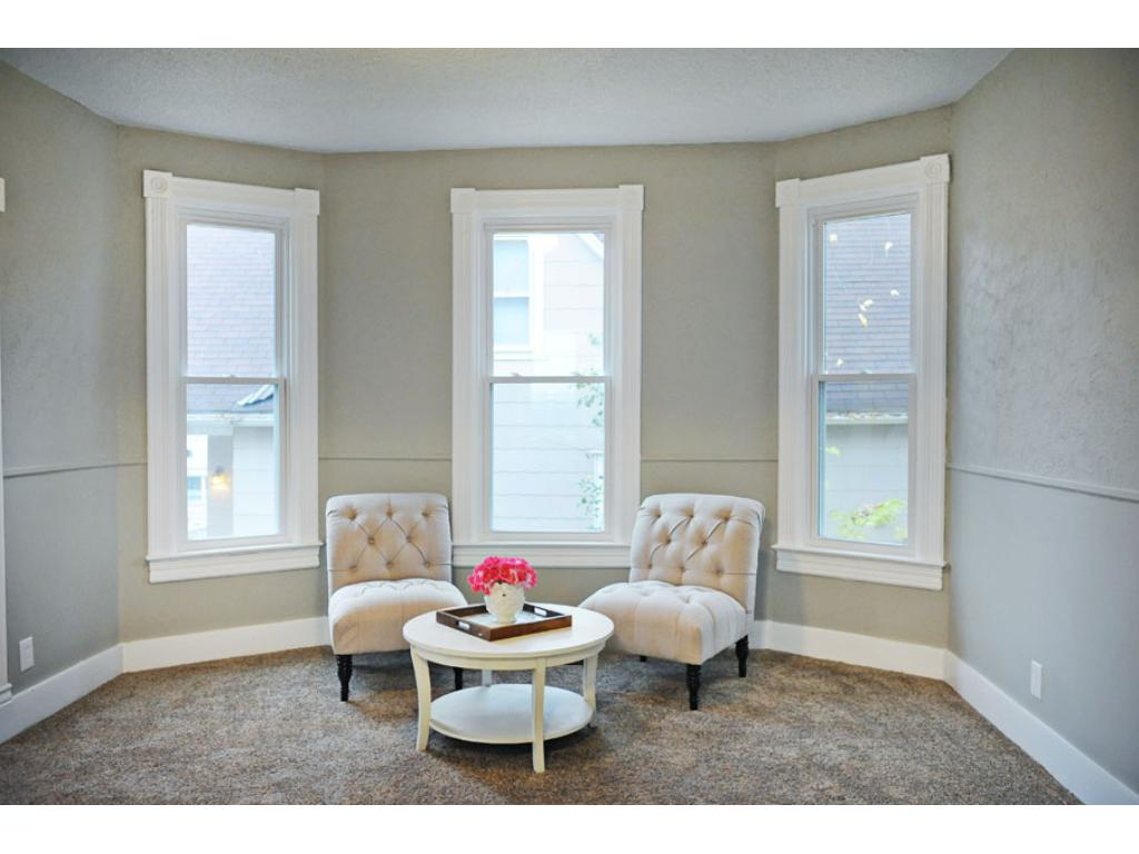 Living and dining room are surrounded by windows