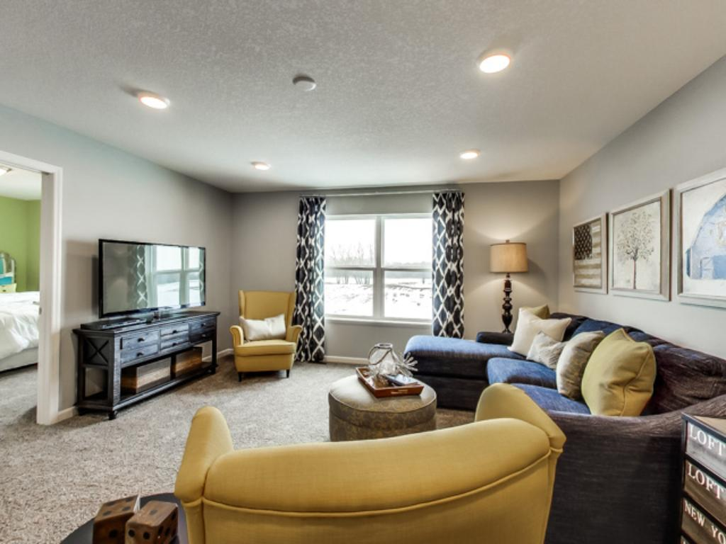 Photo is of the home staged, actual home highlights sweeping vaulted ceilings.
