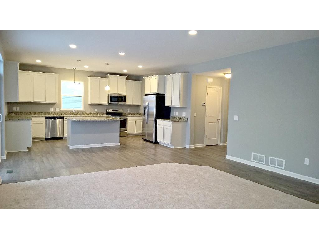 Open kitchen to the family room with cozy fireplace and built-in cabinetry.