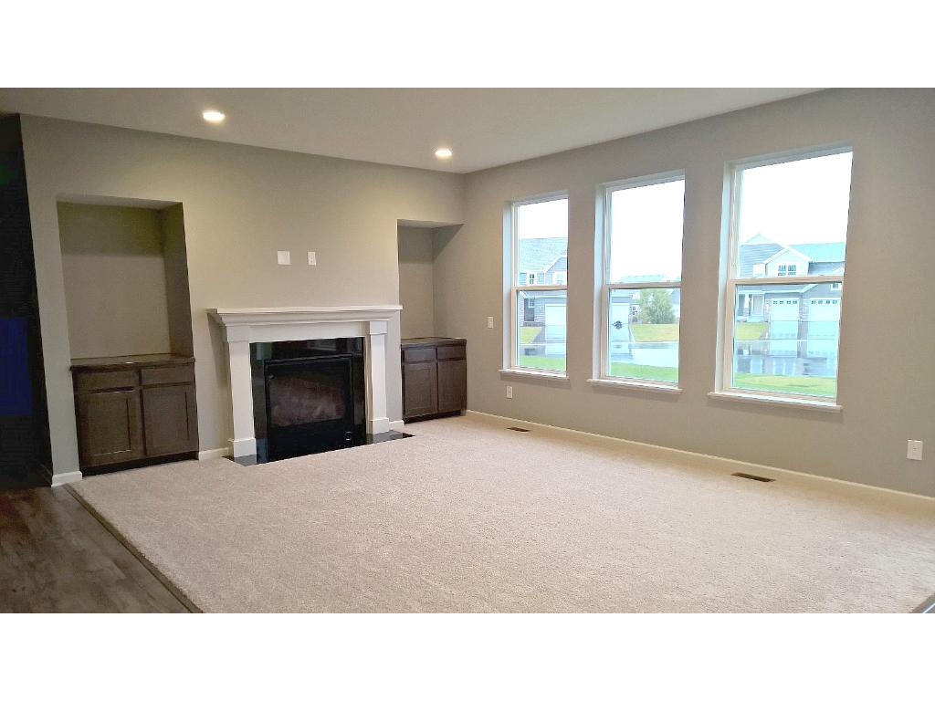 Bright patio doors and wall of windows flood the living spaces with an abundance of natural light. Picture is of similar model and for finished concept.