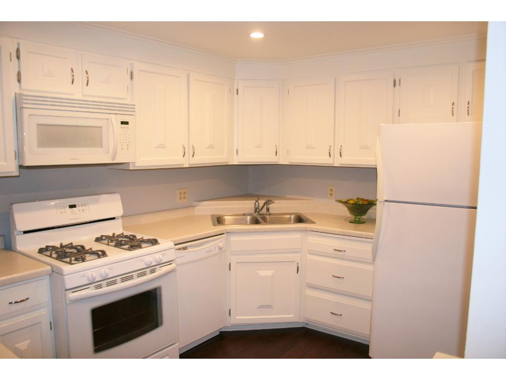 Newly enameled cabinets and gleaming wood floors through kitchen, dining room and hallway.
