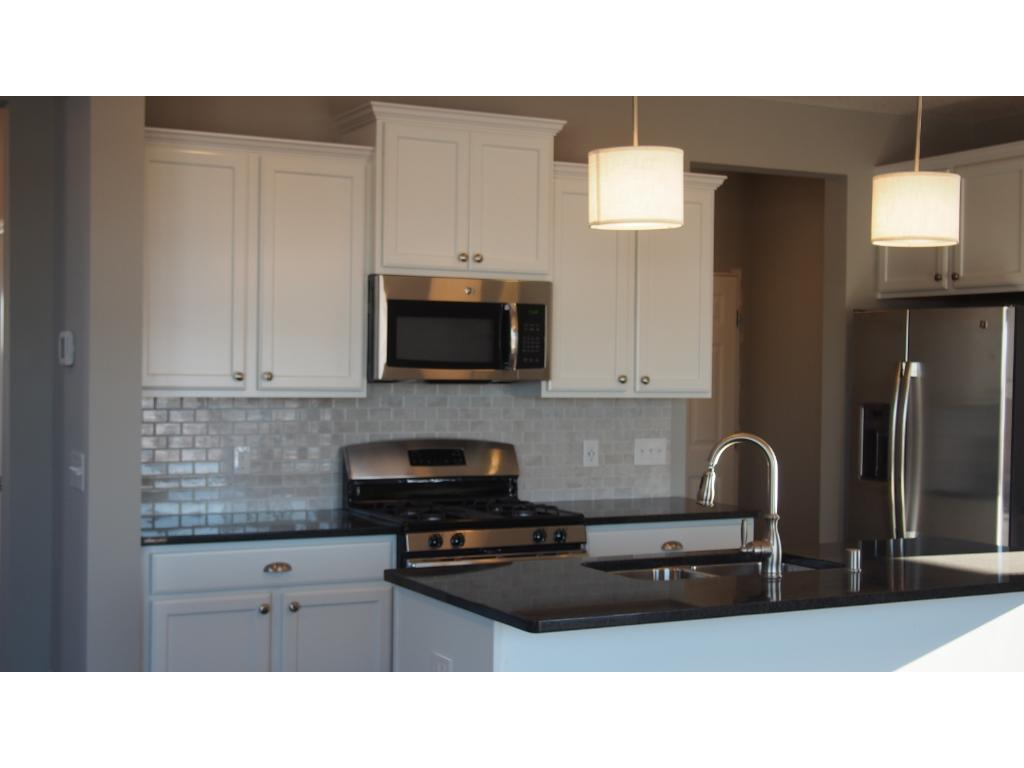 Picture of model.  This home will  also have white cabinets at the perimeter and a stained center island with granite countertops and ceramic tile backsplash.