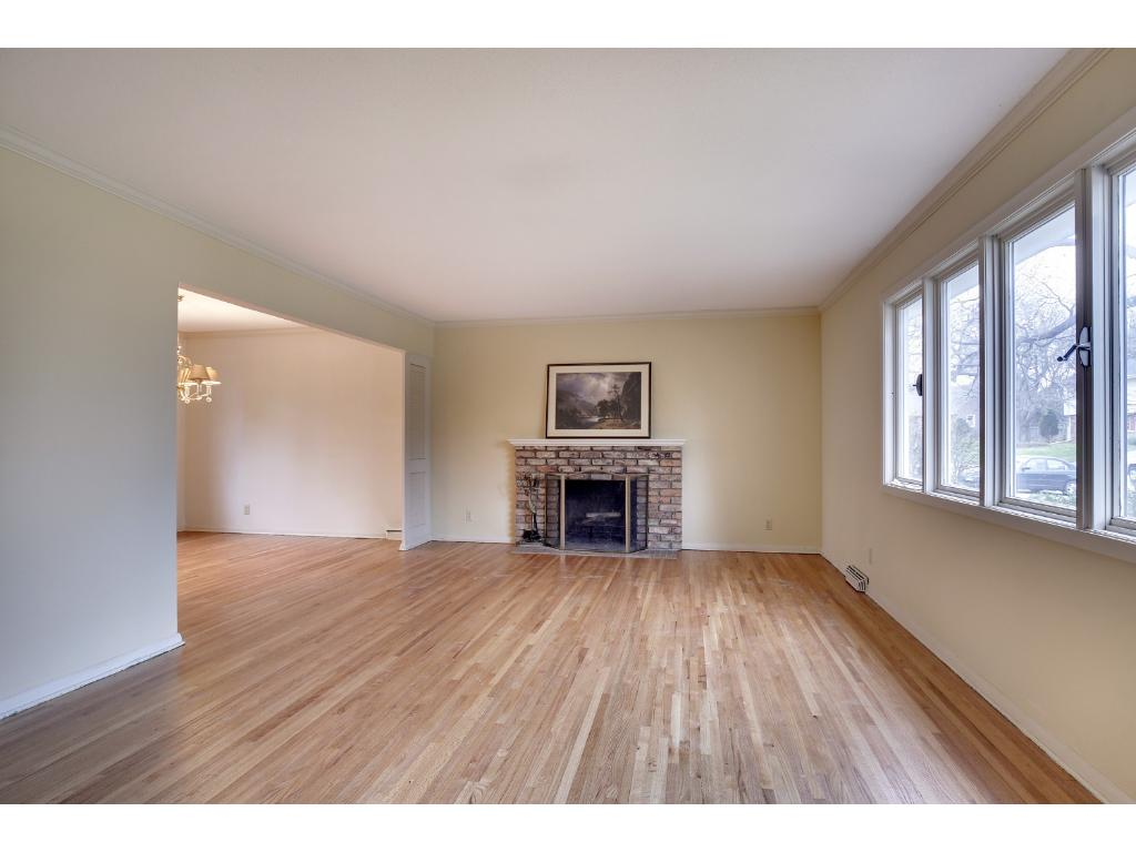 Gleaming hardwood floors in Living Room with wood burning fireplace.
