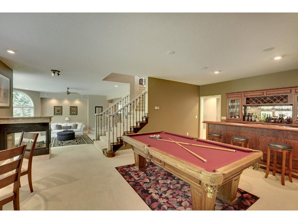 Walking down to the lower level you will notice the staircase is extra wide.  When you reach the bottom, to your right is a pool table that the owner's said can stay - if you want it.  There is also a built in bar, see through gas fireplace.