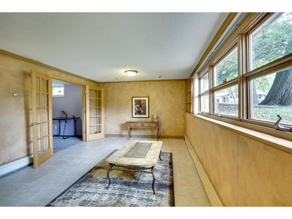 Lower level Family Room with newer flooring and French doors leading to the office.