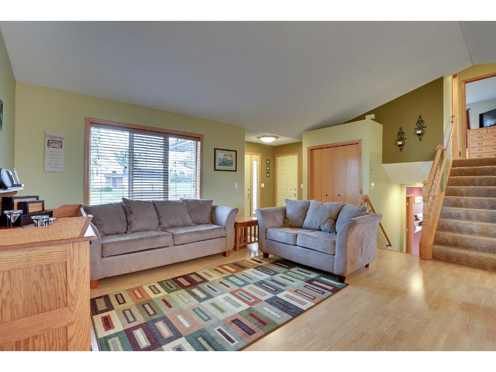 Main level has large open layout for living room, dining room, kitchen, with vaulted ceilings, and patio doors leading to large deck off back of house.