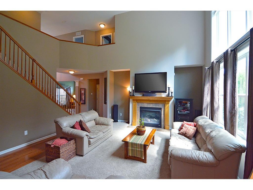 Main level spacious family room with double sided fireplace, vaulted ceilings, and tons of natural sunlight!