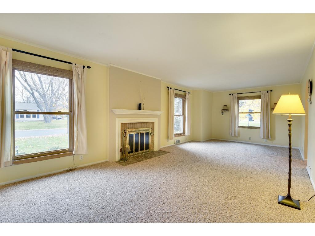Large living room has wood-burning fireplace and hardwood floors under carpet (if you prefer them).