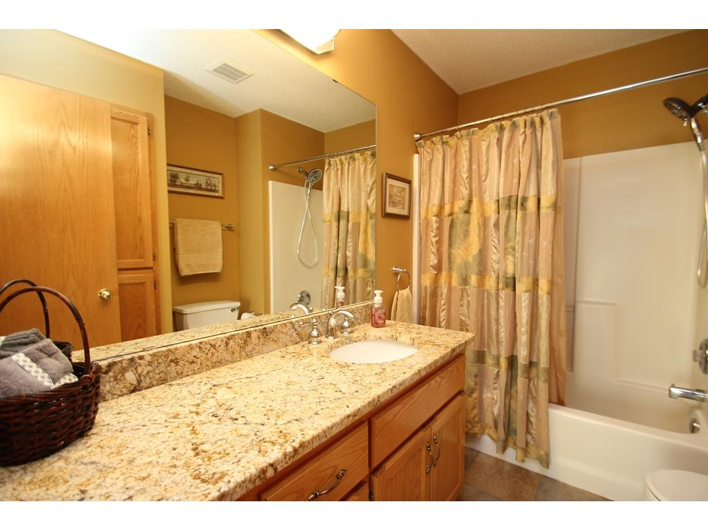 Upper level bathroom with tile flooring, a full tub/shower, and granite countertops!