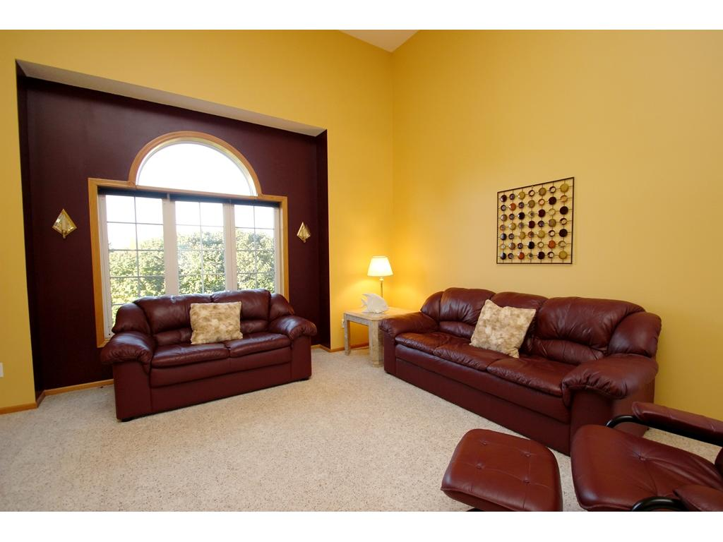 Main floor living room with great natural light and two-story ceilings!