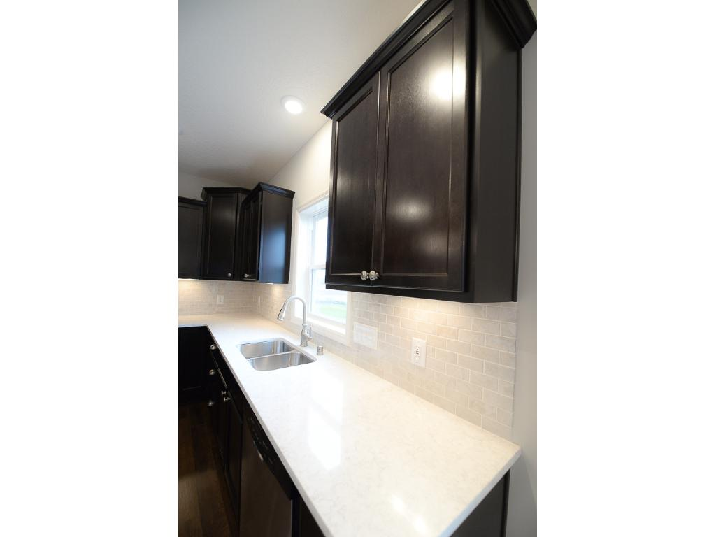 Note the extra details in this kitchen: undercabinet lighting, tile backsplash, undermount sink with stainless steel pull down faucet and quartz countertops~