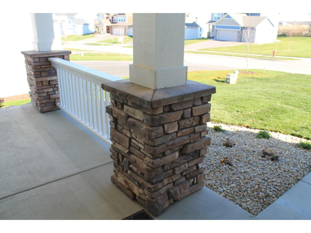 The yard is completely landscaped including rock around the entire home, shrubs and perennials, irrigation and full yard sod. Check out the over sized poured concrete front porch and stone columns. All of these details add to the curb appeal!