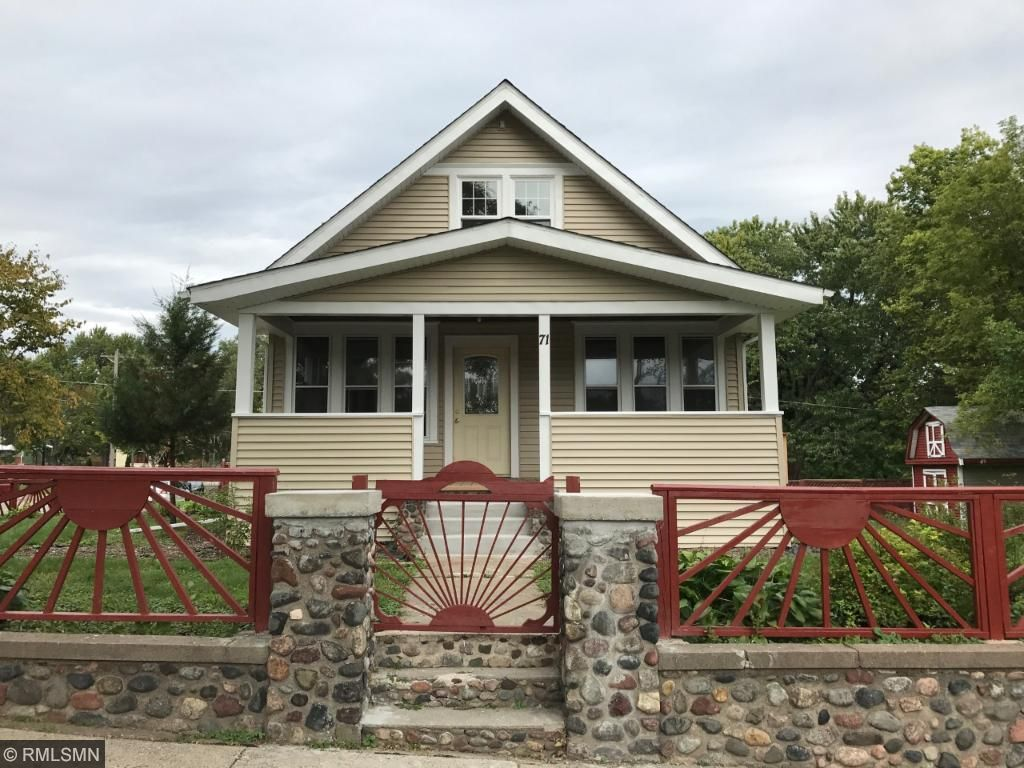 Inviting front of home features a custom fence with large porch