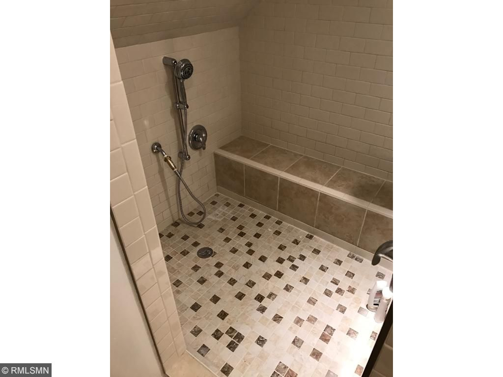 Grand upstairs full-bath with custom tile work and shower heads on both sides of the wall.  Also features large Jacuzzi.