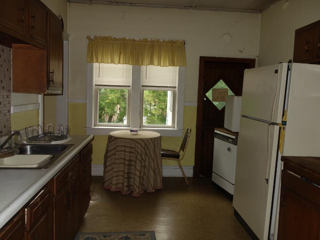 Full kitchen area with a stove & refrigerator - pass thru area to dining room.  Door to 3-season porch.