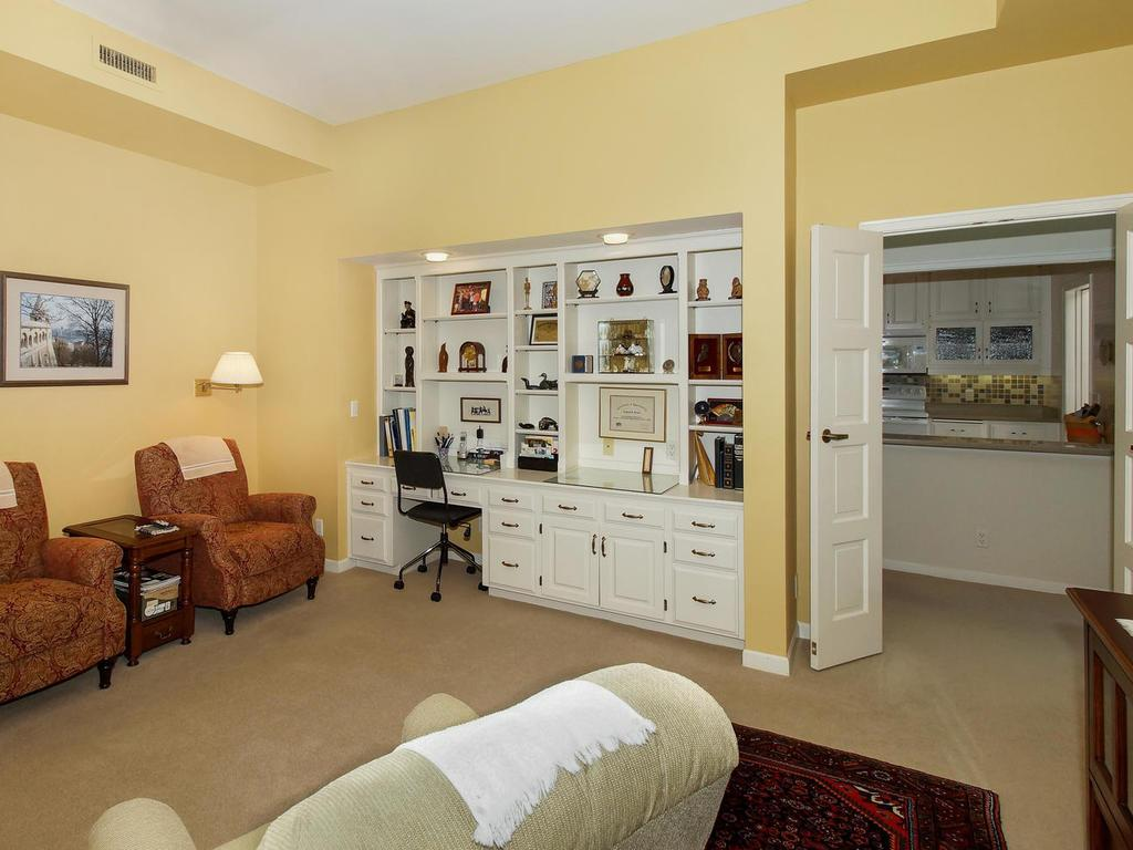 The cozy family room has a built-in desk area, & a cabinet with book shelves.
