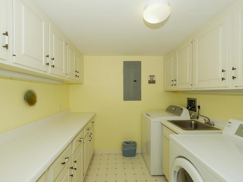Generous sized laundry room with loads of cabinets, folding counter and laundry sink.
