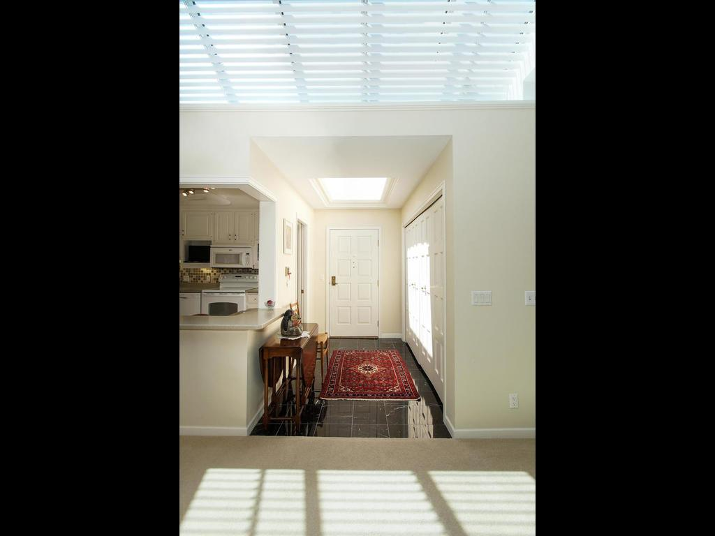 The bright and cheery foyer is loaded with sunlight from the entry skylight.