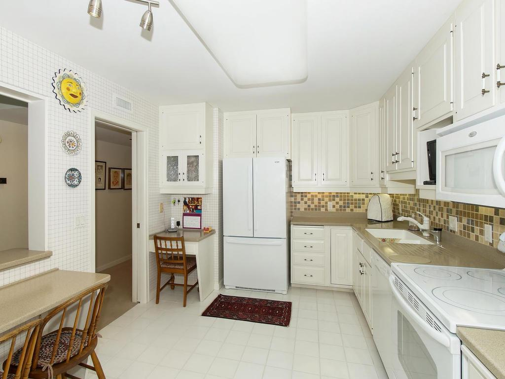 Bright and cheery spacious kitchen with white cabinets, built-ins, and eating bar.