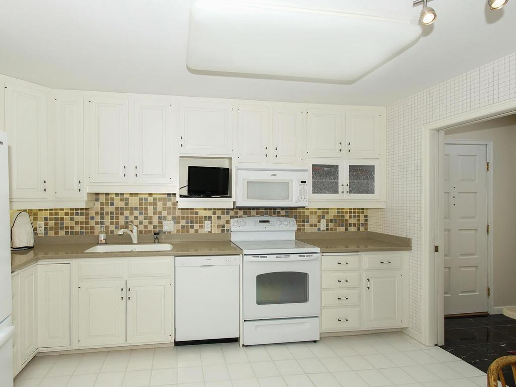 The kitchen is complimented by Corian counters, tile backsplash, and ceramic tile floor.