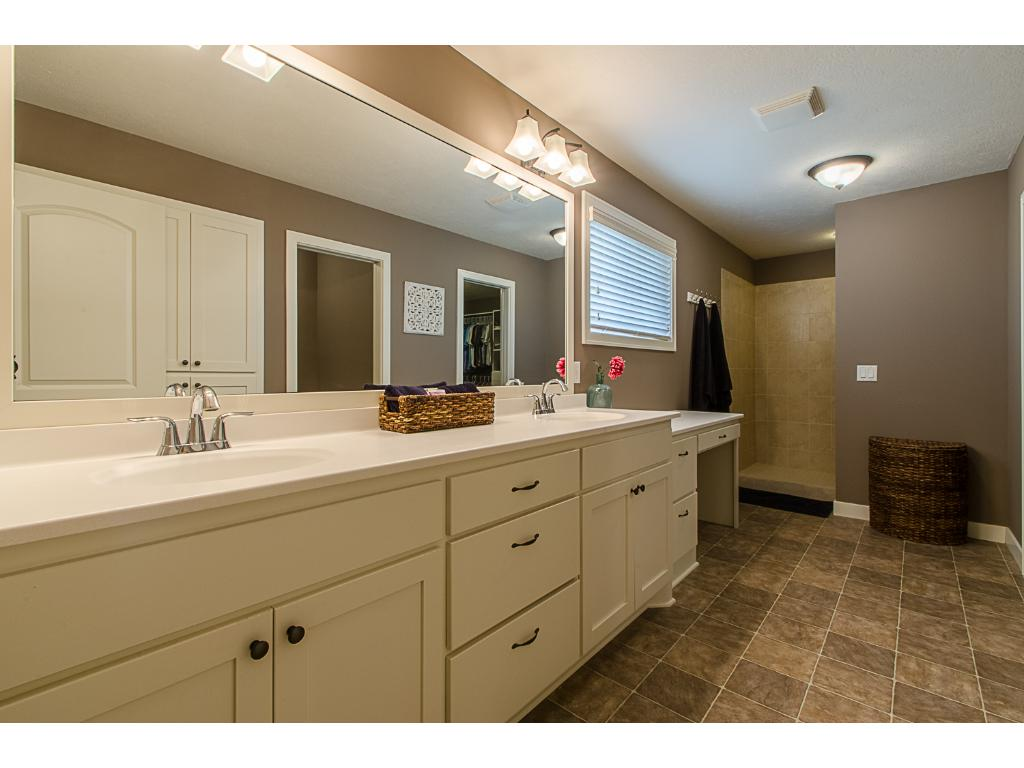 Master bathroom has dual sinks, a makeup vanity, dual-head tiled shower with bench seat, private water closet, and vast amounts of storage.