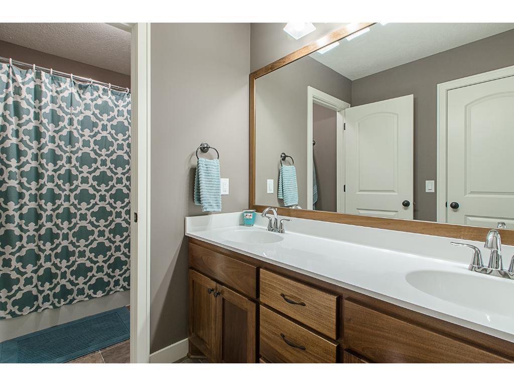 Upper level bathroom has two sinks, nicely framed mirror, and a private commode and bath/shower area.
