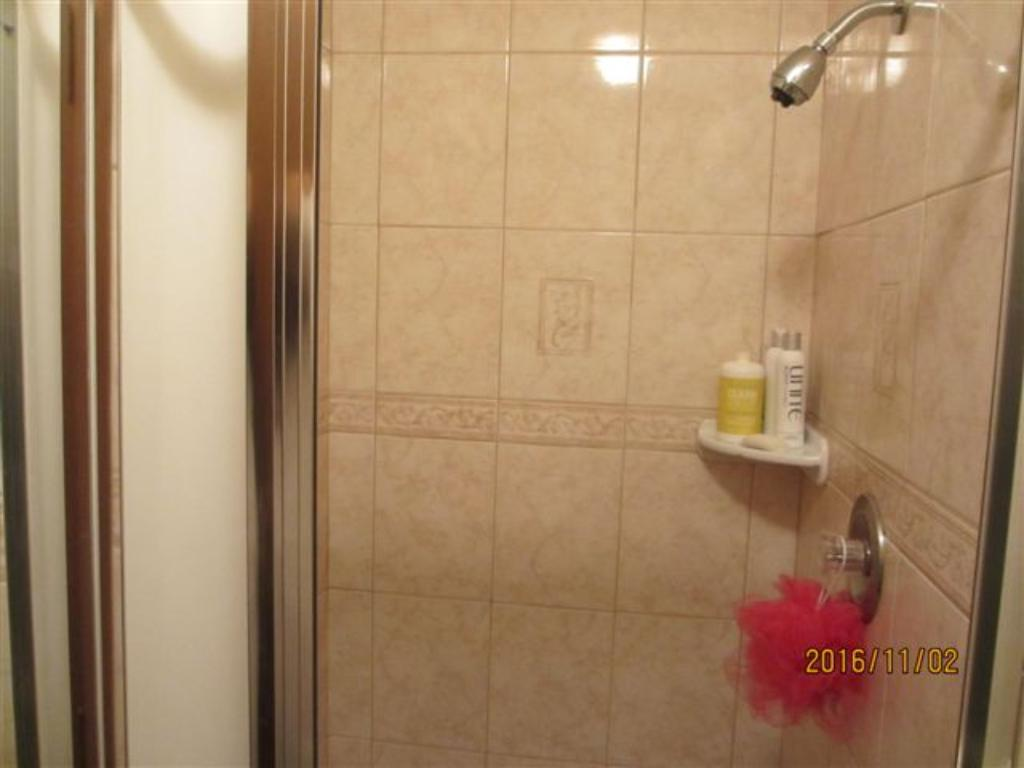 Shower in the master suite that is newer with attractive tile.