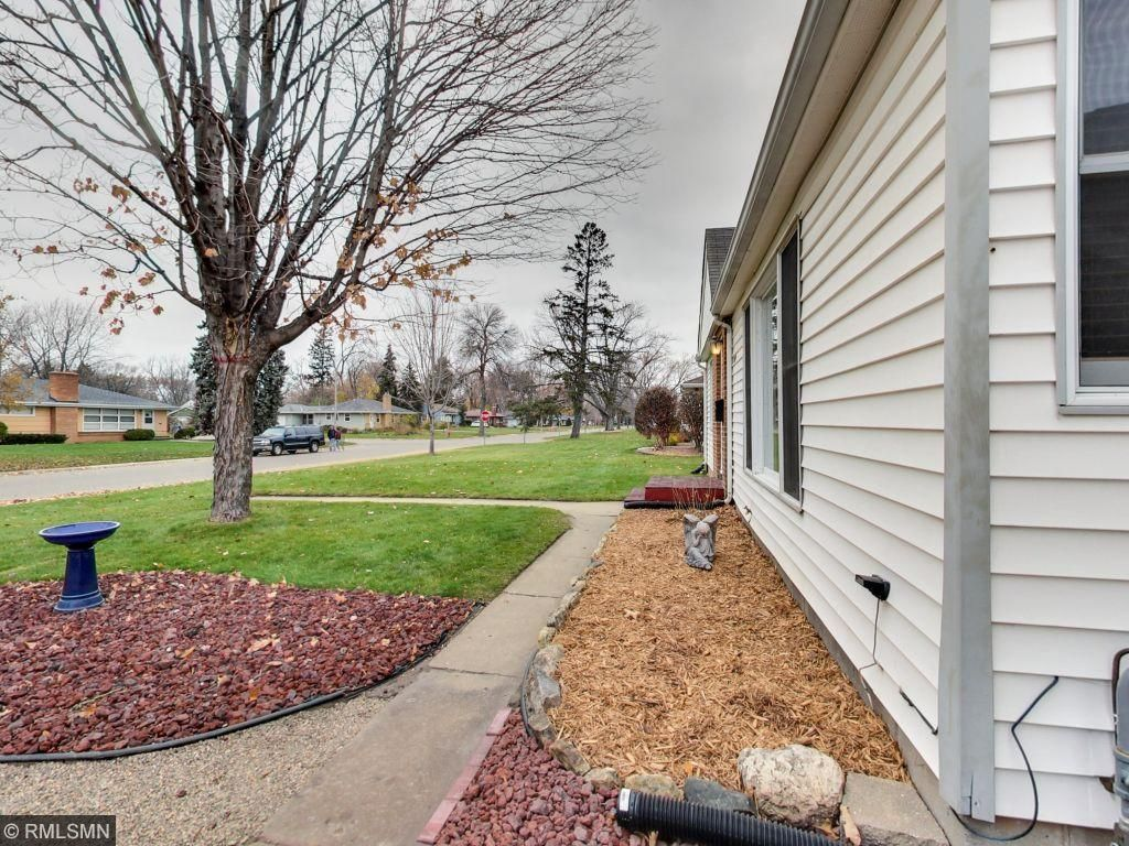 Fresh landscaping and large cement driveway.