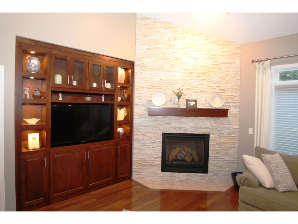 Stone tile fireplace surround and impressive entertainment built-ins complete with accent lights.