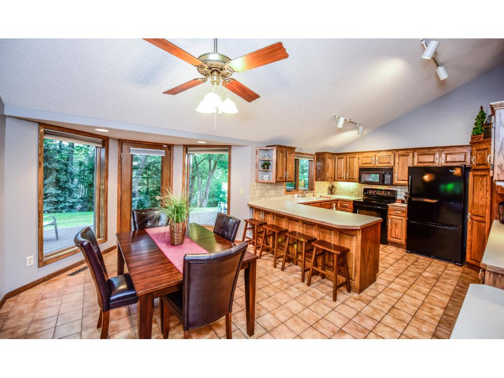 Tile floors in the kitchen with beautiful cabinets, black appliances, and a large eat in kitchen area with windows that overlook the yard.