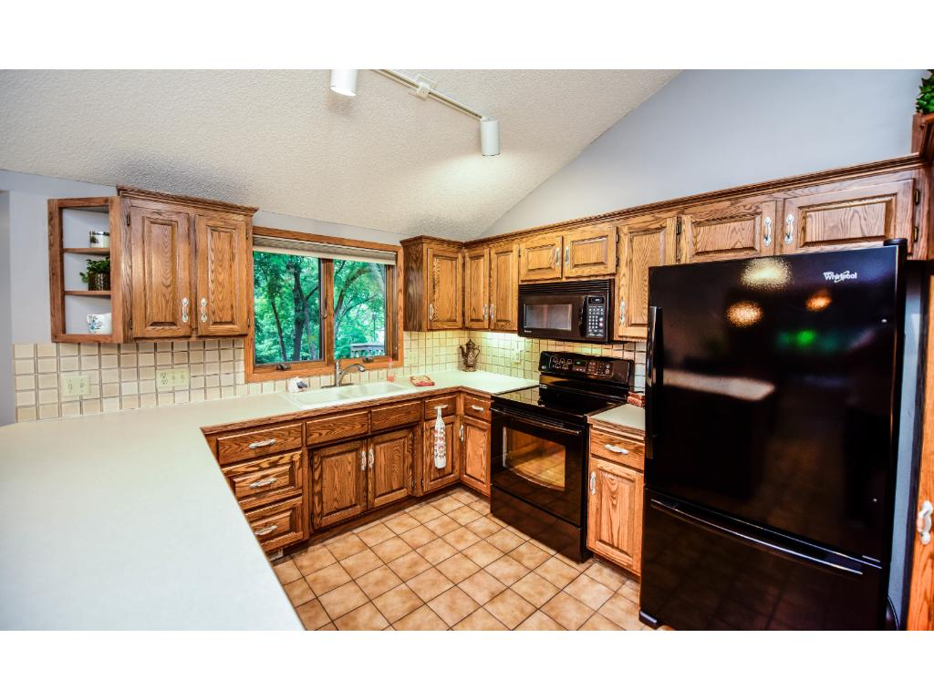 Tile back splash and plenty of cabinets compliment the kitchen along with vaulted ceilings.