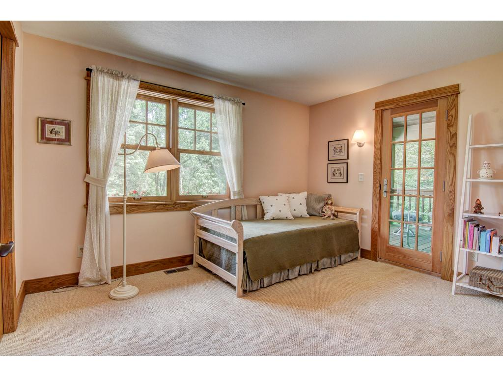This bedroom, one of three on the main floor, has a door to the balcony porch and a spacious walk-in closet.