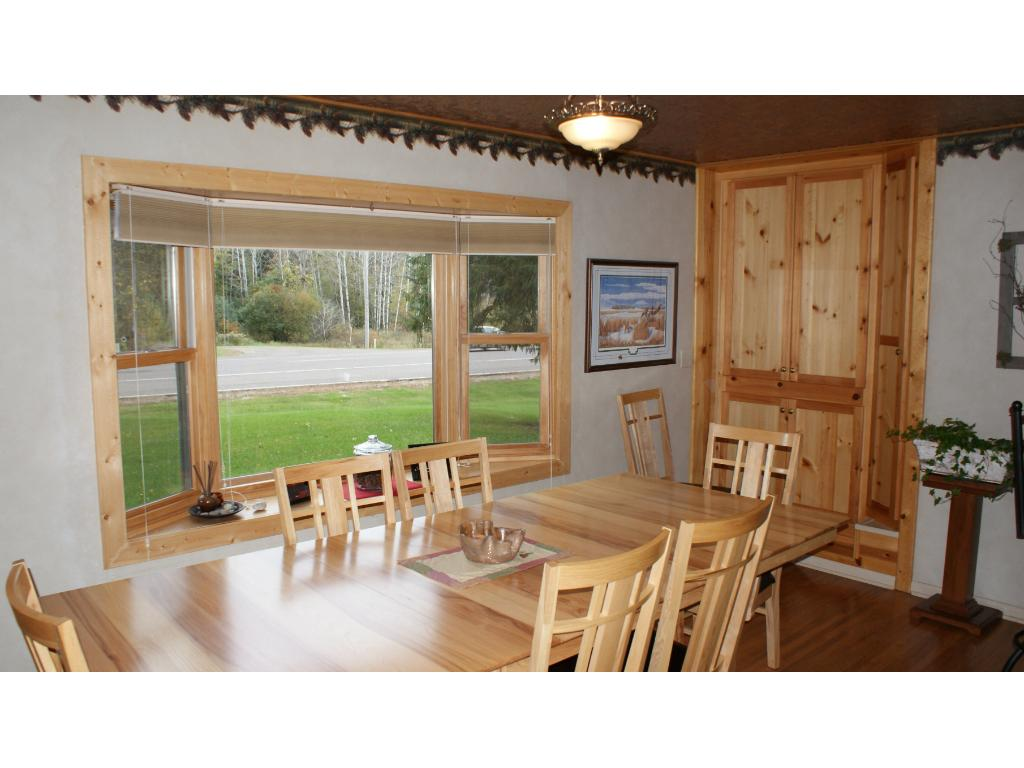 Dining room with large window and pull out drawers in storage cupboards.