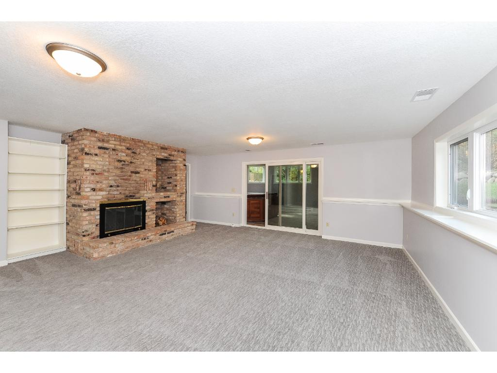 Family Room with Wood Burning Fireplace and New Carpet