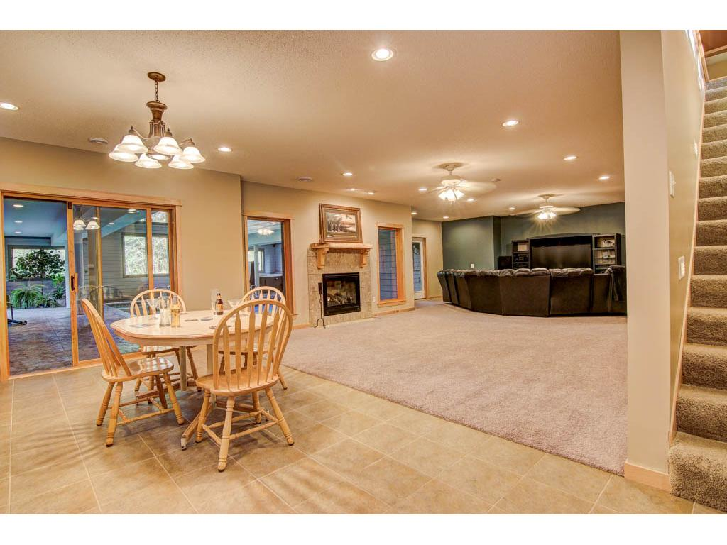 Lower Level kitchen area with a refrigerator,  sink and lots of cabinetry.A gas fireplace and a spacious family room. This room has sliding doors to the pool area.