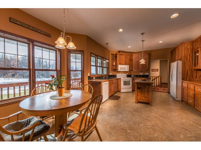 large eat in kitchen with island/ Custom Oak cabinets and large kitchen windows which bring in tons of lighting.